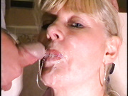 Older blonde looks into the cam while swallowing