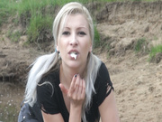 A blonde suckles on a cock while outdoors