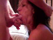 A brunette is held by her hair while gobbling up a cock