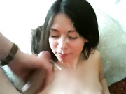 A cute Asian in lingerie gets sprayed with cum