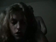 A slim blonde with smallish tits fucked in a dark room
