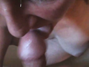 A mature brunette with saggy tits is sucking cock